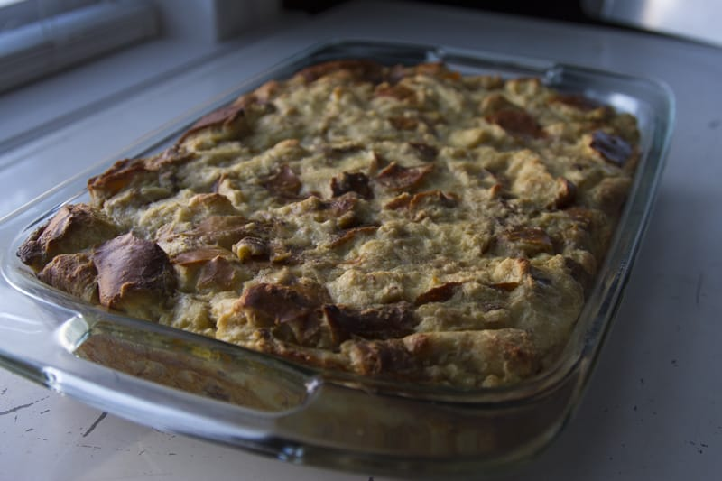 Finished pretzel bread pudding in a glass baking dish cooling on a white table top near a window.