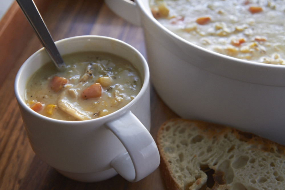 A mug of chicken pot pie soup with a spoon in it. A pot of soup and some crusty bread sit beside it.