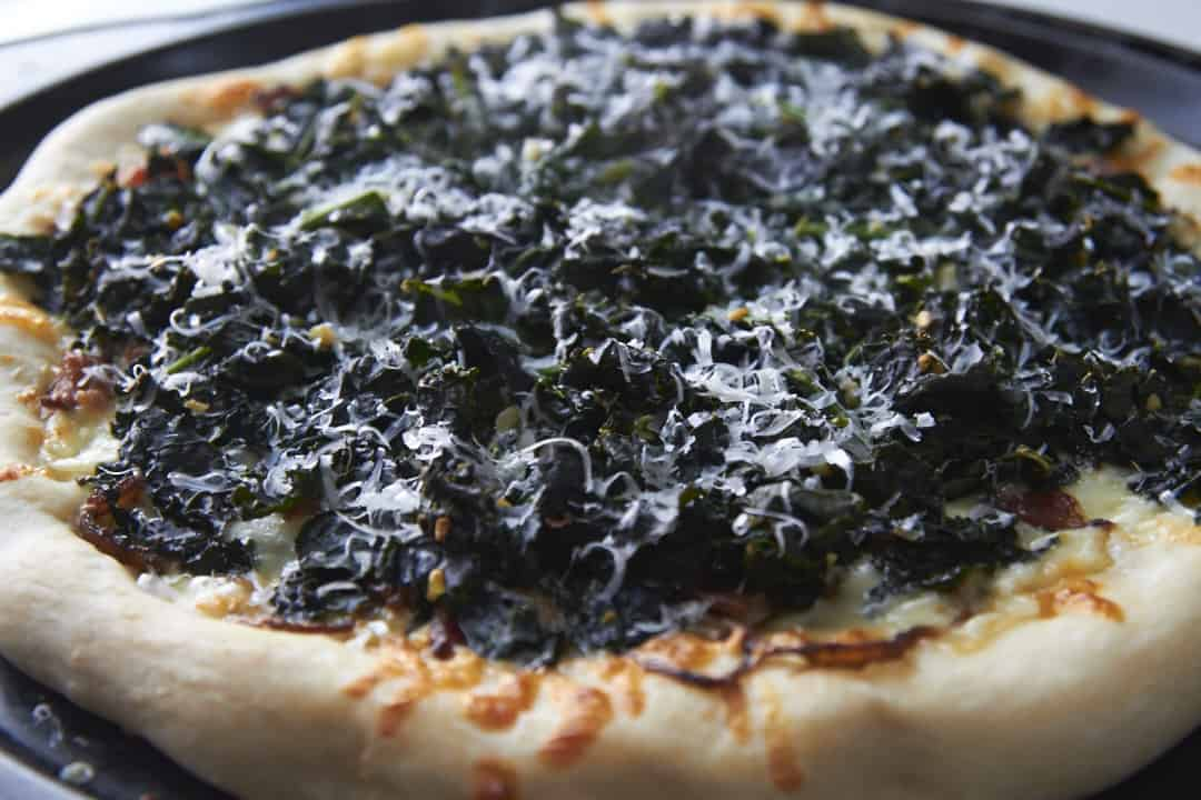 Homemade pizza with kale, bacon and caramelized onions.
