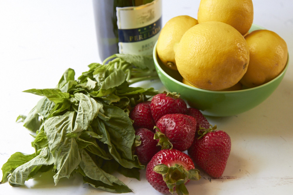 A bowl of lemons, some fresh strawberries, a bunch of fresh basil and a bottle of Prosecco on a white surface.