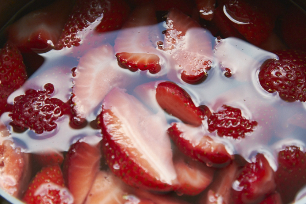 Sliced strawberries submerged in water.