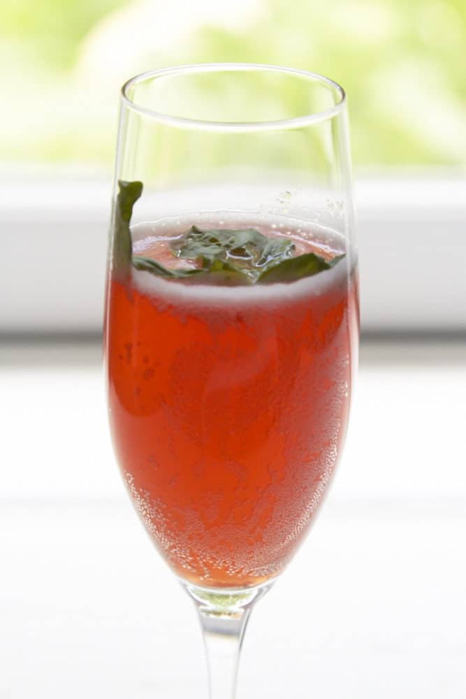 Alcoholic punch with Prosecco strawberry and basil in a champagne glass garnished with basil.