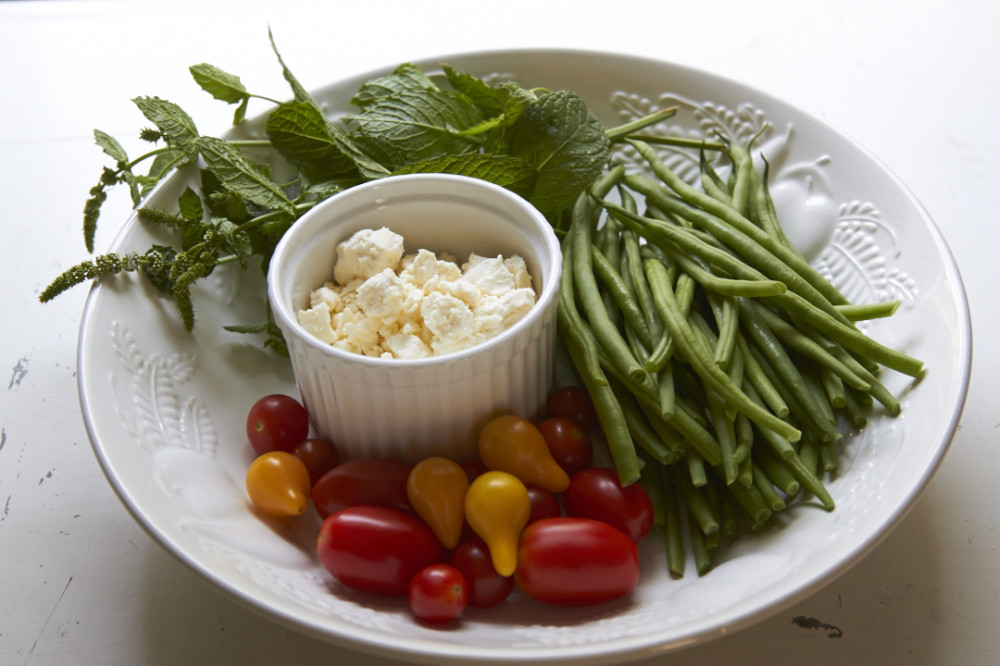 Fresh mint, green beans, tomatoes, and feta chees in a large white bowl.