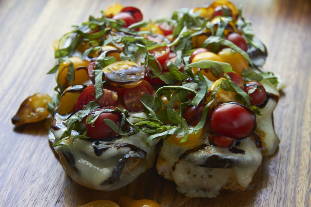 Open-faced eggplant caprese sandwich topped fresh tomatoes, basil and balsamic reduction.