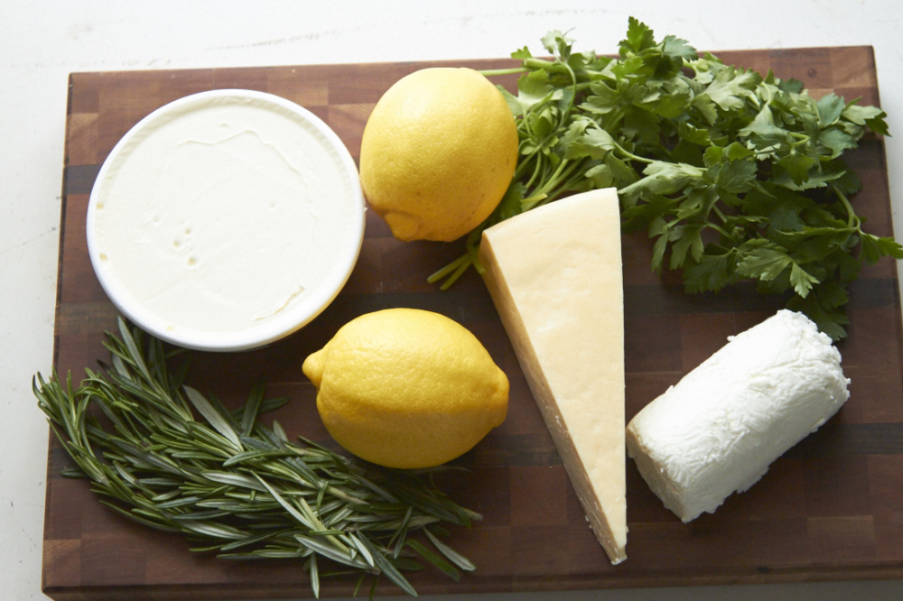 Mascarpone, goat cheese, parmesan and fresh herbs on a wooden cutting board.