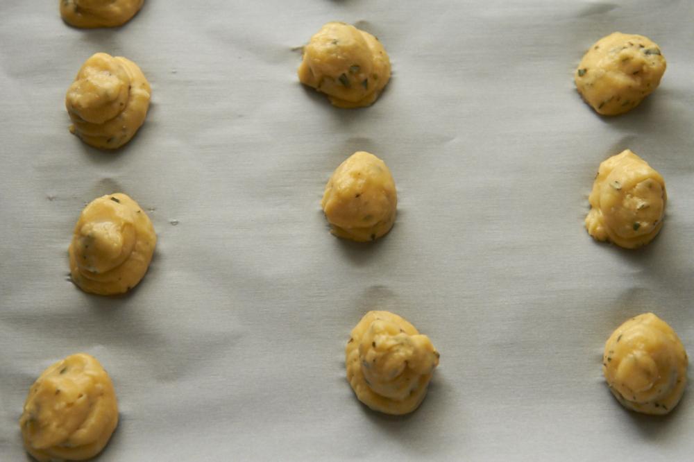 Pâte á choux dough for gougères on parchment paper.