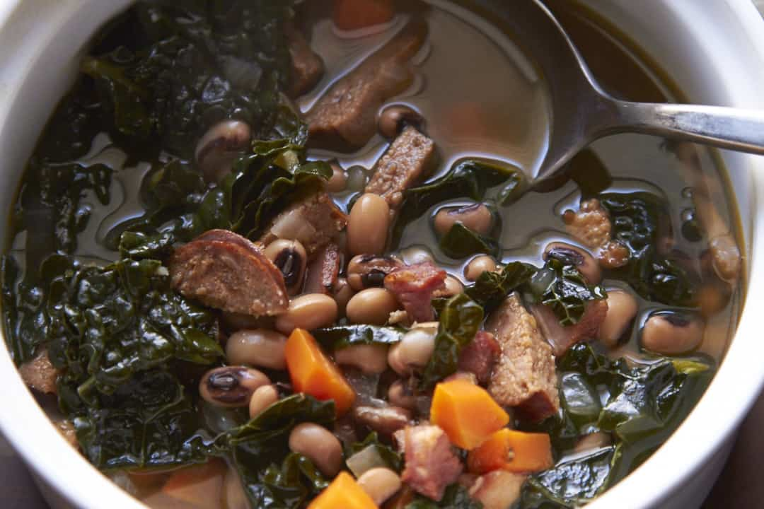 A bowl of New Year's Day Soup, with black-eyed peas, smoked sausage and kale.