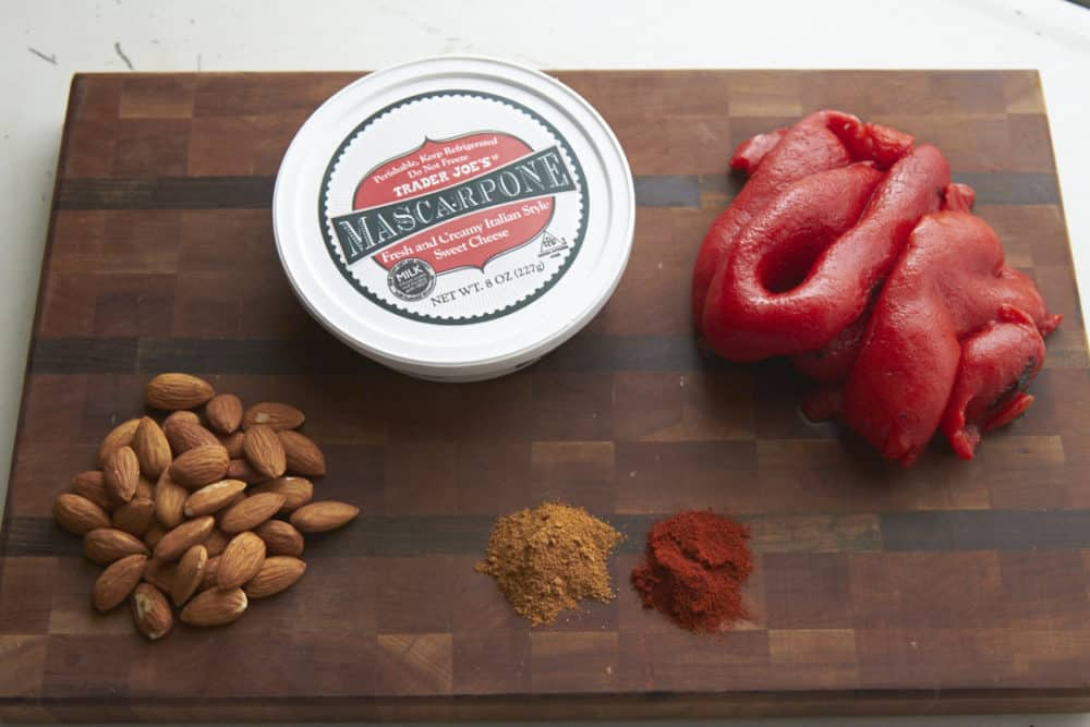 Ingredients for roasted red pepper dip on a wooden cutting board including mascarpone cheese, roasted red peppers, almonds and spices.