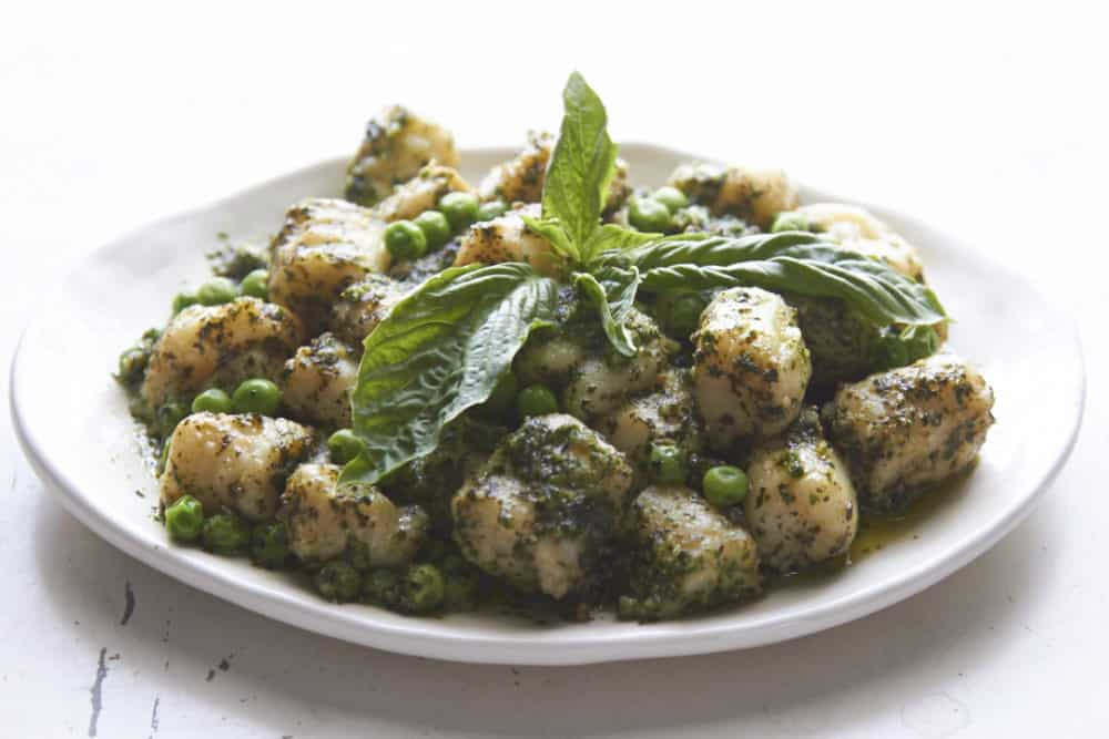 A plate of gnocchi with peas and pesto.