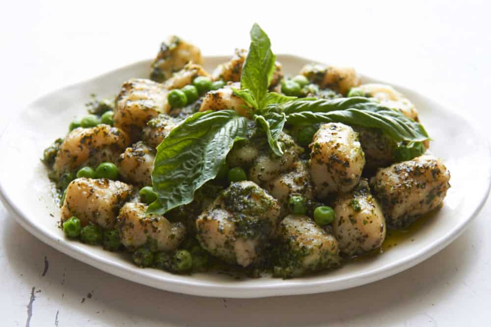 Gnocchi with peas and pesto on a white plate.