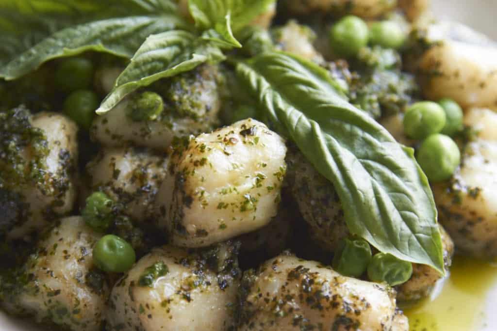 Closeup of gnocchi with peas and pesto.