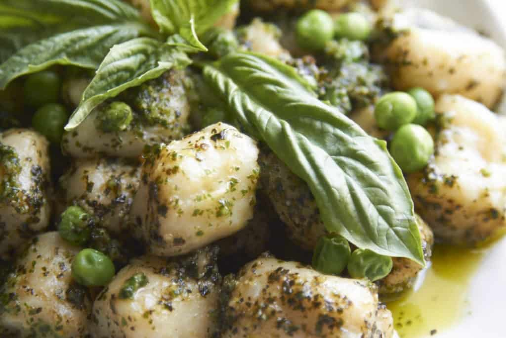 Closeup of gnocchi with pesto and peas garnished with fresh basil.