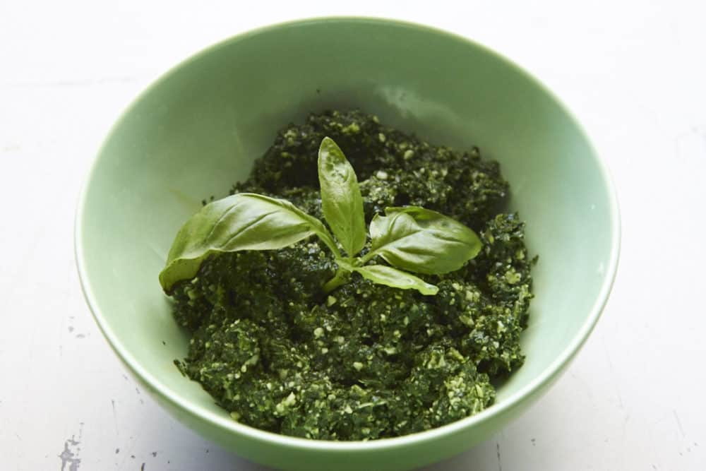 Kale pesto in a green bowl, topped with fresh basil leaves.