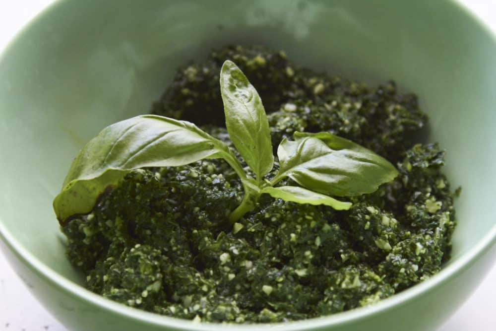 Kale pesto in a green bowl garnished with fresh basil.