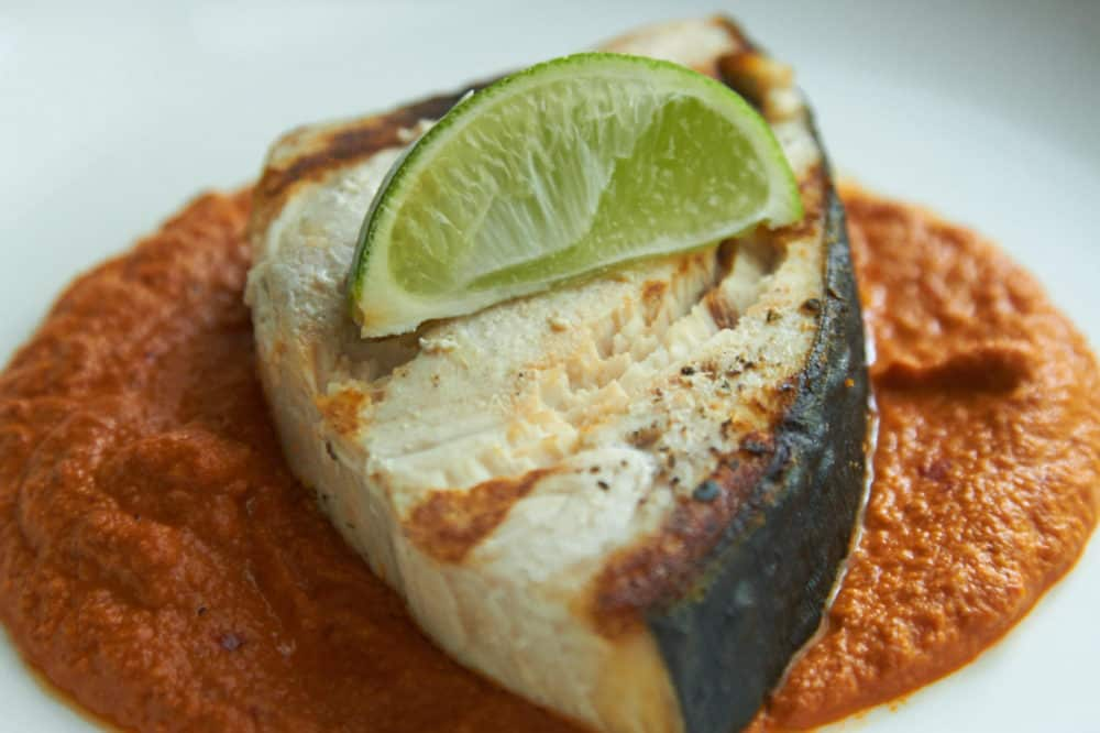 Grilled halibut with Almond orange mole, garnished with a lime wedge.