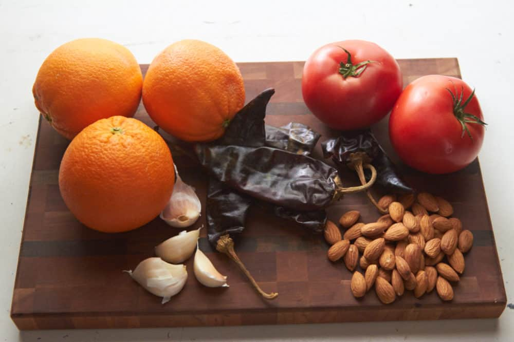Oranges, tomatoes, guajillo chiles, almonds and garlic displayed on a cutting board.