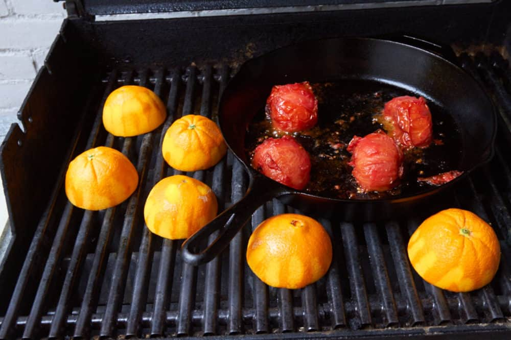 Tomatoes in a cast iron skillet and orange halves all roasting on a grill.