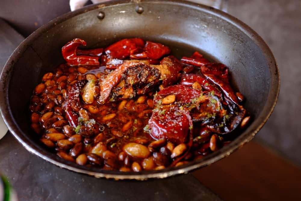 A skillet filled with almonds, chiles, tomatoes, garlic, honey and spices.