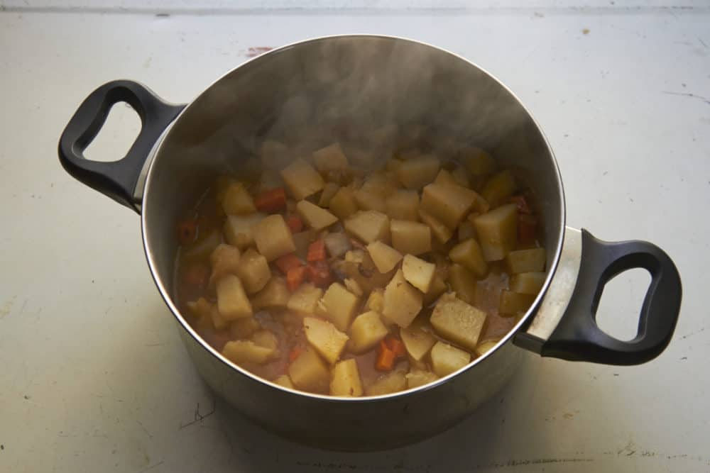 A deep pot filled with steaming potatoes and carrots in chicken stock.
