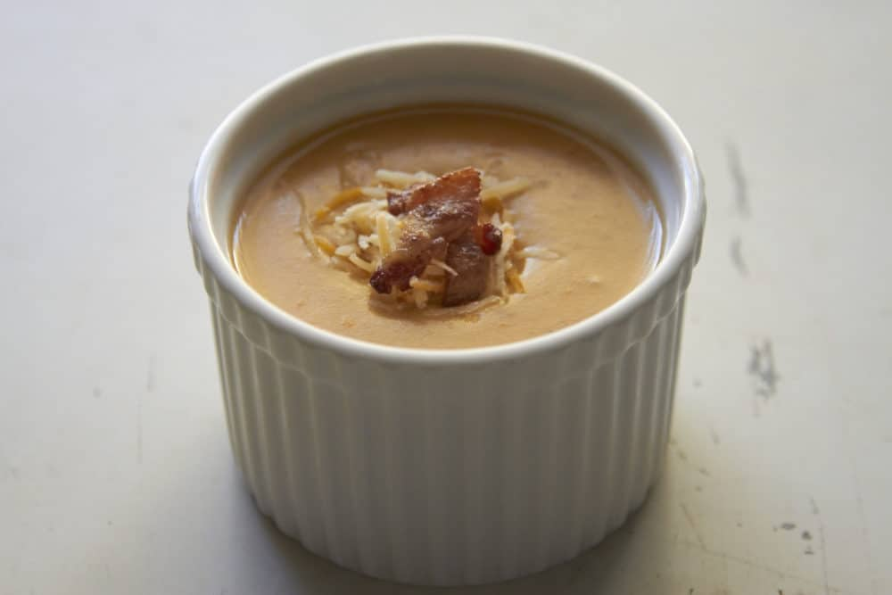 A white soufflé bowl filled with Cheesy Potato Soup with Bacon and Beer. The soup is topped with shredded cheese and crumbled bacon.