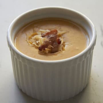 A small bowl of Beer Cheese Potato Soup, topped with crispy bacon and shredded cheese