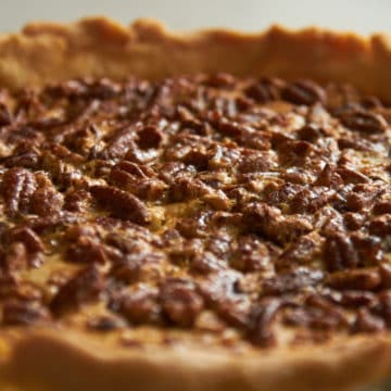 Close up of a whole pecan cream cheese pie