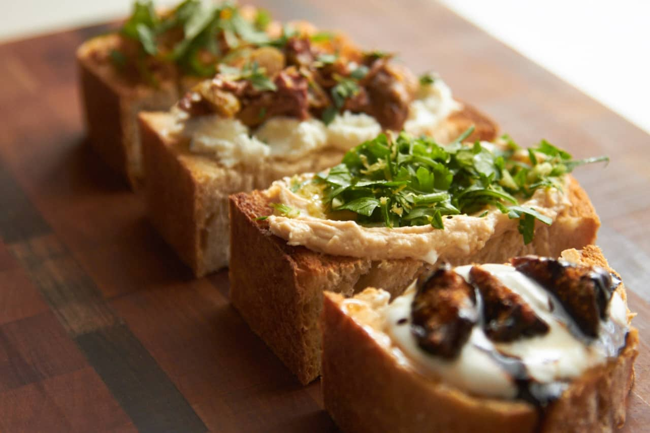 Four different bruschetta recipes displayed on a cutting board, with goat cheese, hummus, olive tapenade and other ingredients.