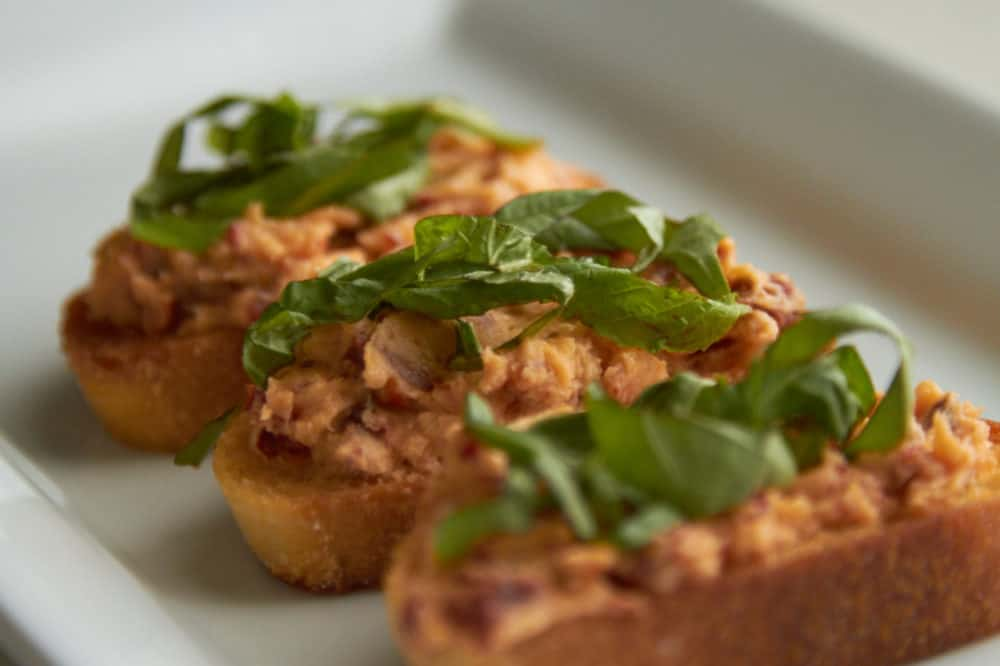 Crostini with sun dried tomato mascarpone topped with fresh basil on a white plate.