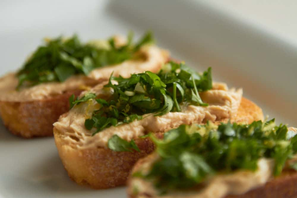 Crostini with hummus and gremolata on a white plate.