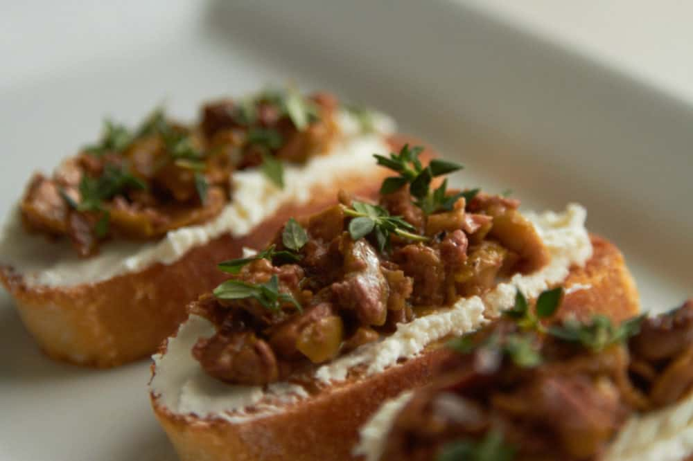 Crostini with goat cheese, olive tapenade and fresh thyme on a white plate