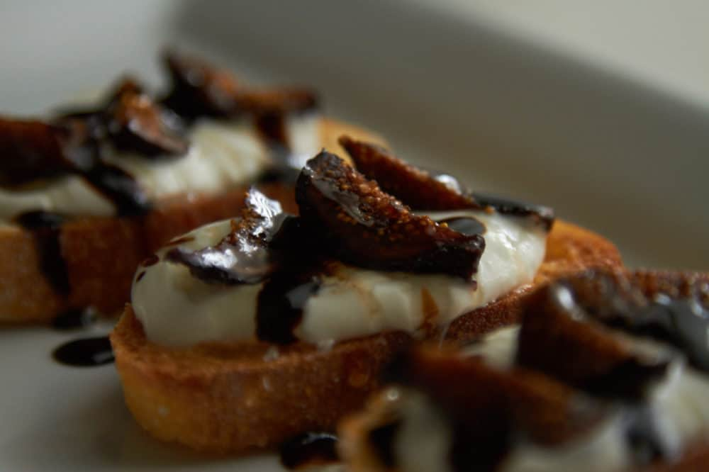Crostini with whipped goat cheese, figs and balsamic glaze on a white plate.