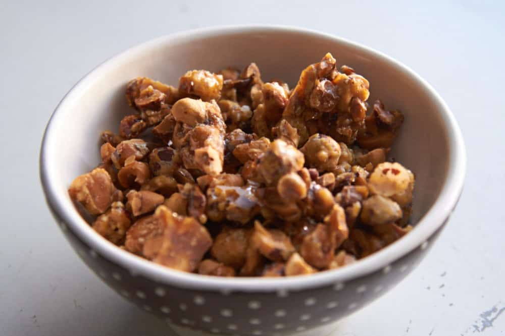 Candied hazelnuts in a brown and white polka dot bowl.