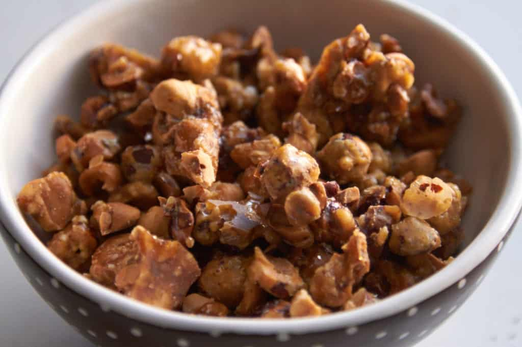 Candied hazelnuts in a bowl that is brown with white polka dots.