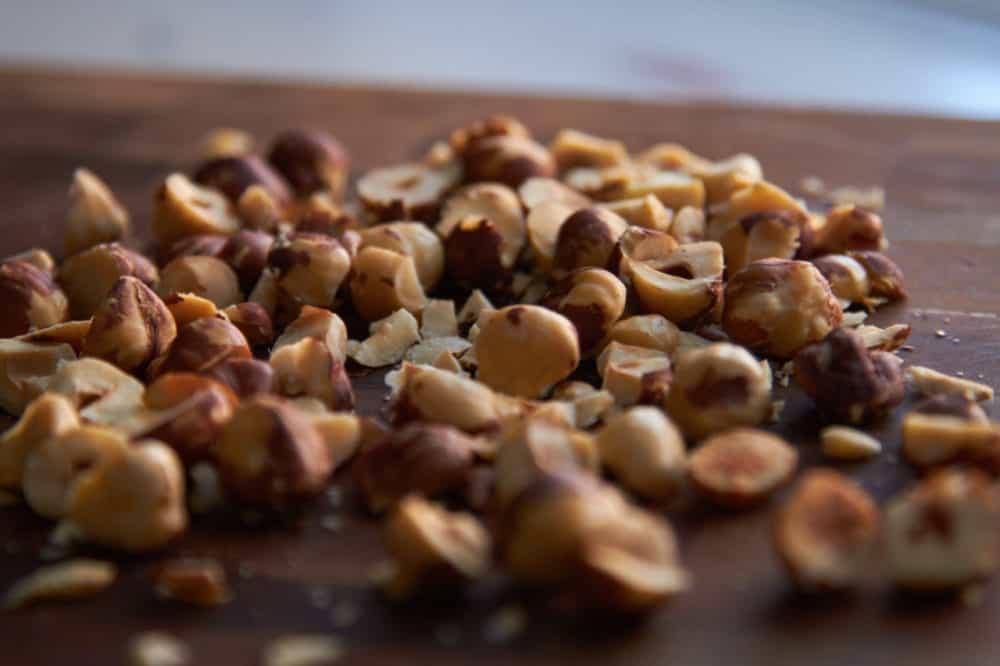 Chopped raw hazelnuts on a wooden cutting board.