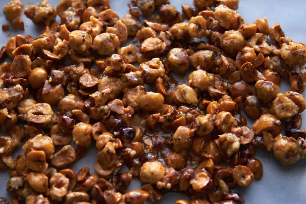 Candied hazelnuts cooling on parchment paper.