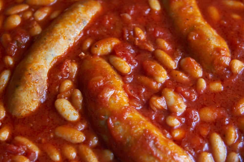 Sausages and cannelini beans in tomato sauce.