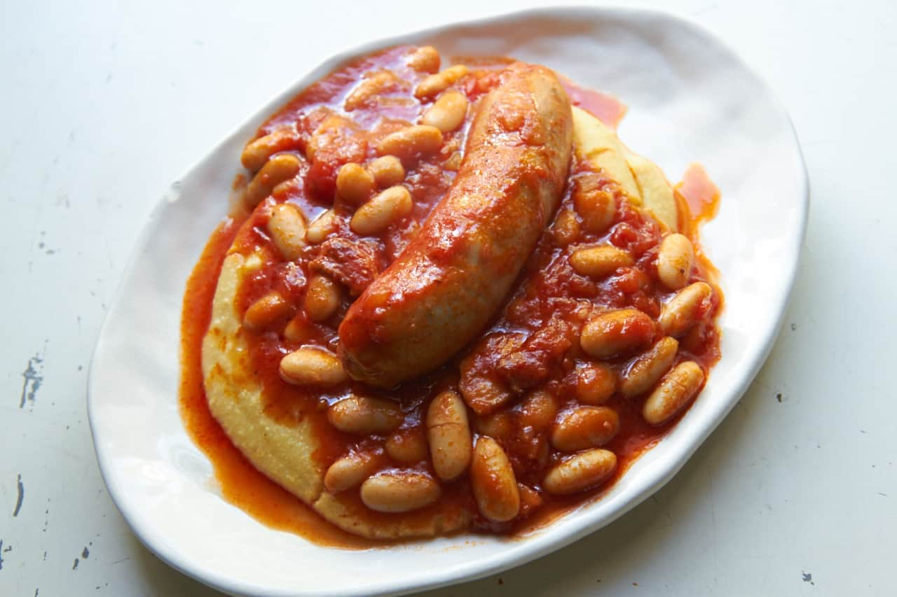 Sausage and cannelini beans in tomato sauce over polenta on a white plate.