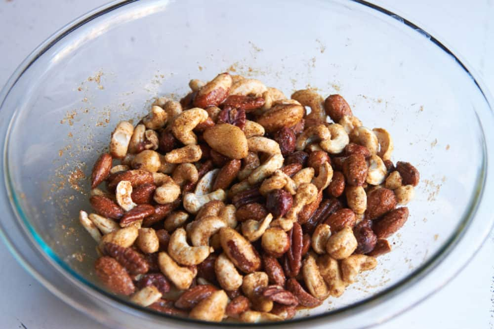 Mixed nuts coated with egg whites and spices in a glass bowl.