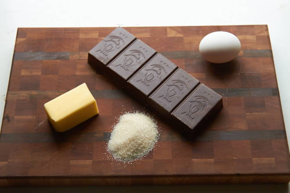 Chocolate, sugar, butter and egg on a cutting board