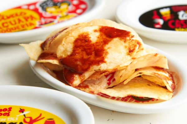 Potato chips with paprika sauce surrounded by colorful plates.