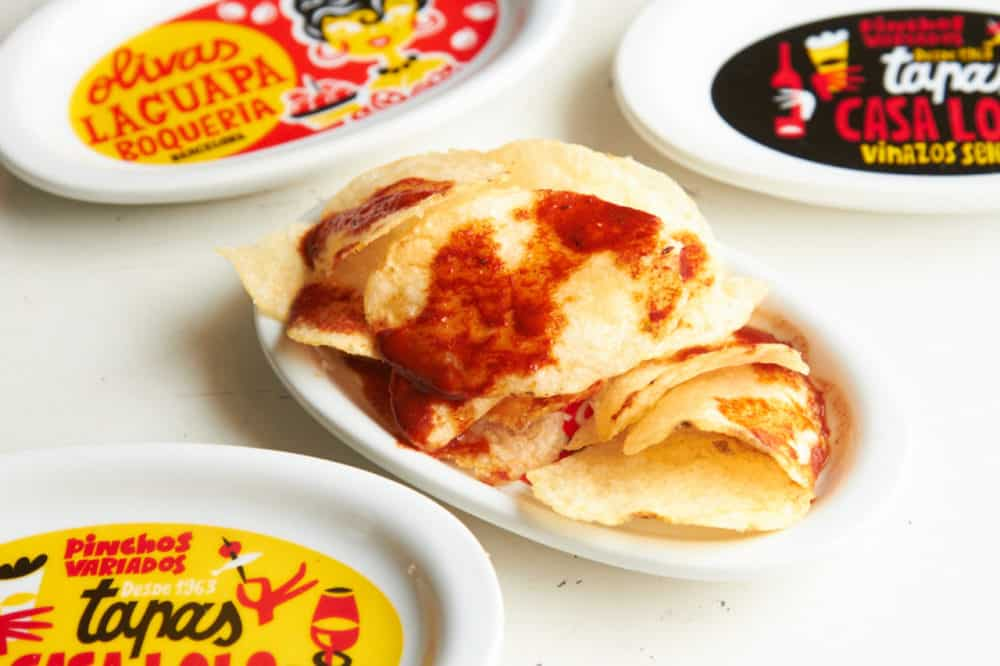 Paprika chips on a small plate surrounded by plates that are red, black and yellow with Spanish phrases written on them.
