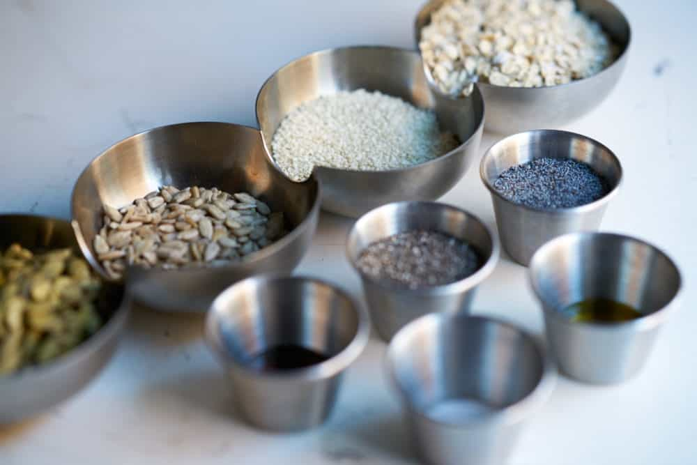 Small metal bowls filled with seeds, oil and seasonings.