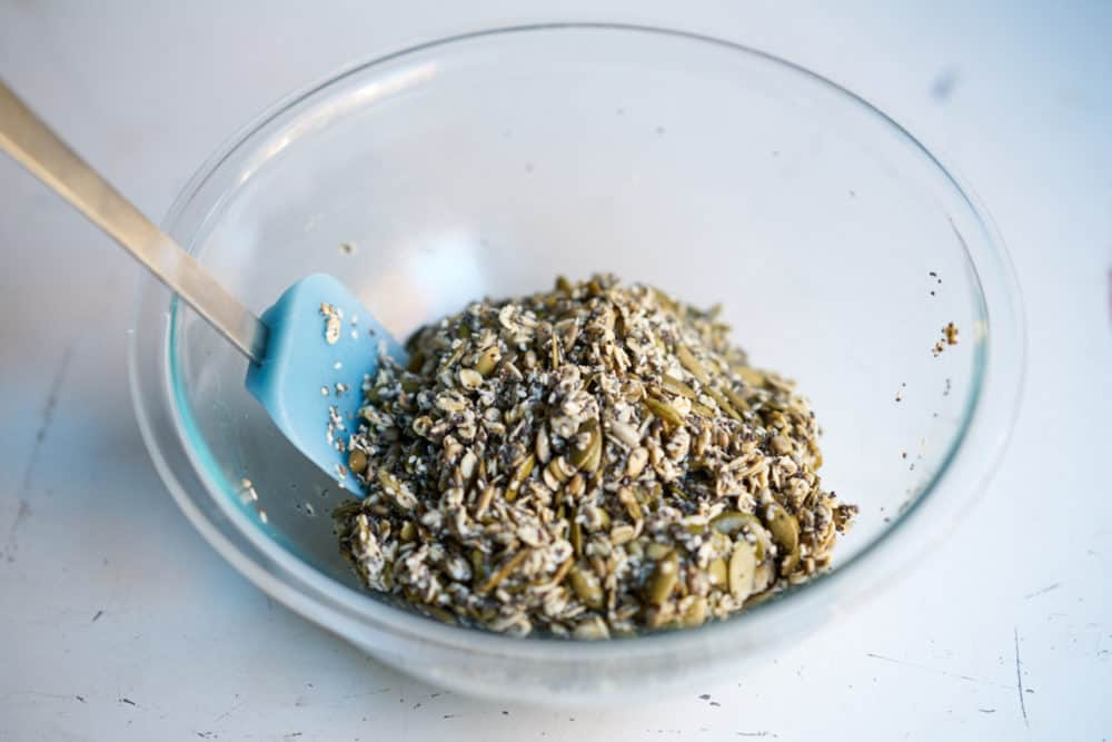 Seeds, oats, maple syrup, water and oil combined in a bowl to make cracker dough.