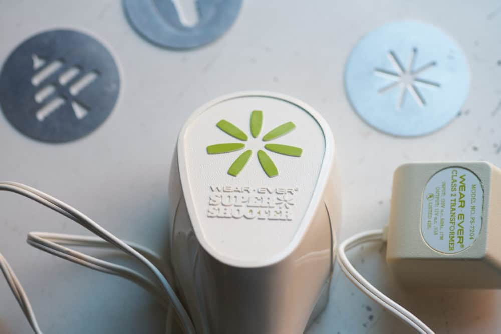 An electric cookie press with wording that says Wear Ever Super Shooter, surrounded by small metal discs for making cookies of various shapes.