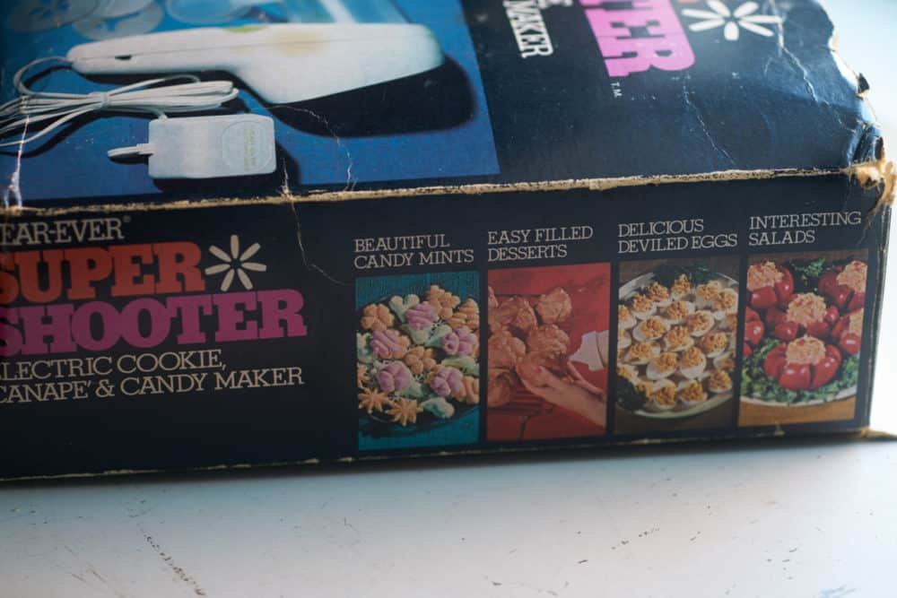 "Box for a 1970's cookie press with vintage photos along the side showing ""beautiful candy mints"", ""easy filled desserts"", ""delicous deviled eggs"", and ""interesting salads."""