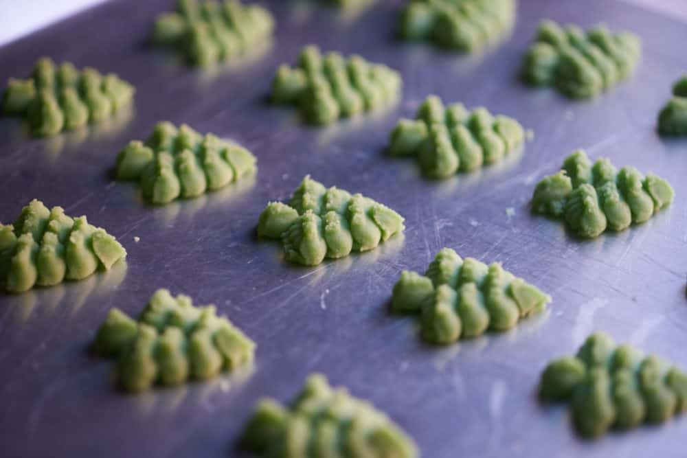 Side view of several green, Christmas tree shaped cookies on a silver cookie sheet waiting to be baked.