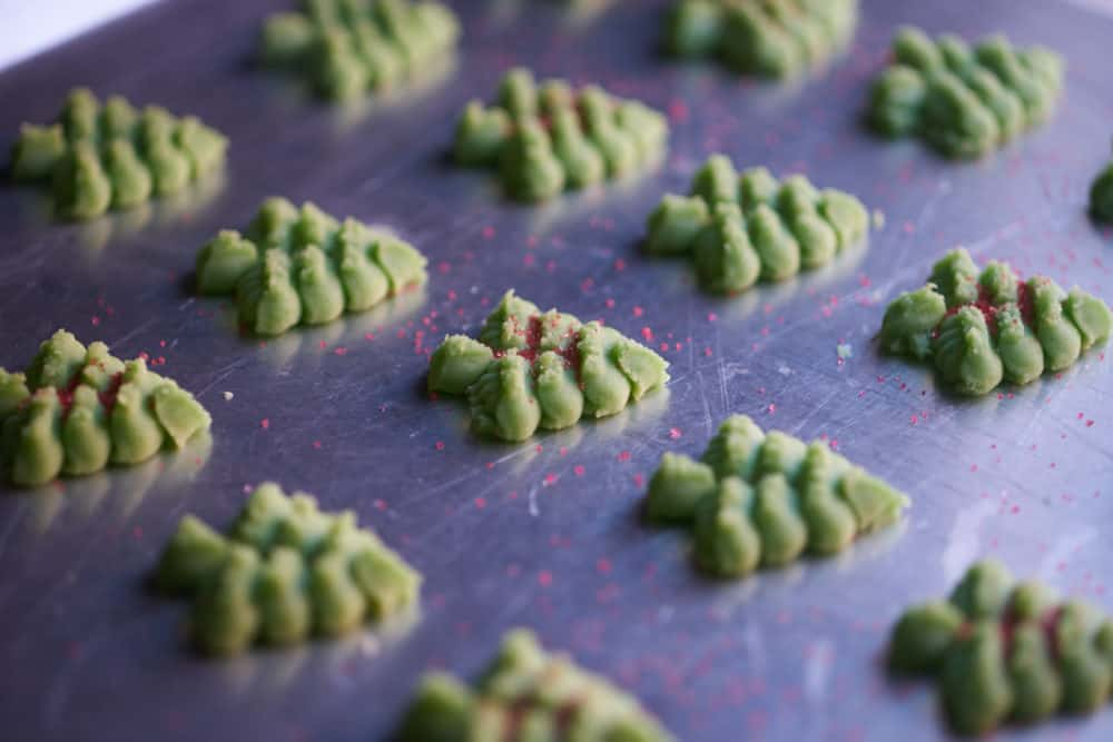 Side view of several green, Christmas tree shaped cookies on a silver cookie sheet waiting to be baked, some with red sugar sprinkles on top.
