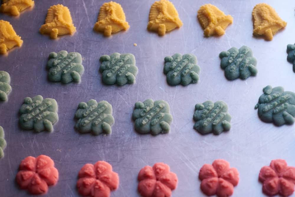 Christmas cookies on a cookie sheet waiting to be baked, in the shape of gold bells, blue ornaments, and red wreaths.