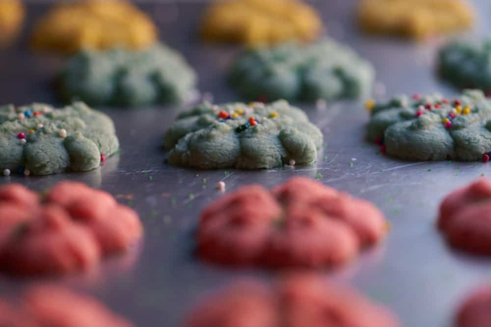 Colorful, baked Christmas cookies on a cookie sheet, decorated with non pareils and sugar sprinkles. Gold bells, blue ornaments, and red wreaths.