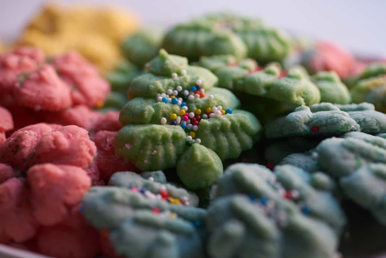 Colorful Christmas cookies o f various shapes and colors, including red wreaths, gold bells, blue ornaments and green Christmas trees. A green Christmas tree-shaped cookie with multicolored non pareils is centered.